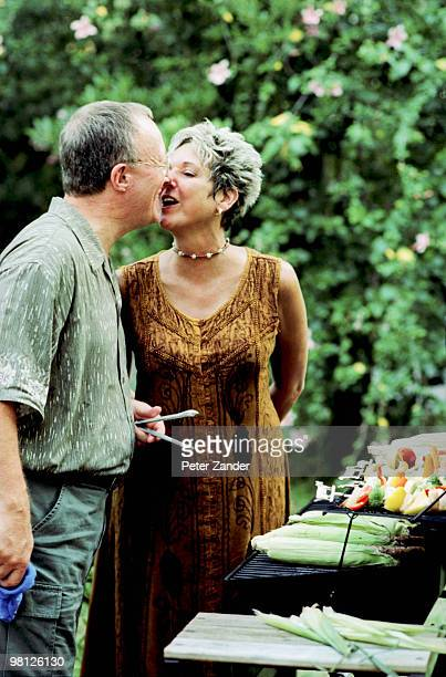 Couple kissing in front of grill