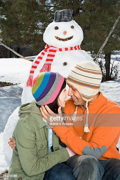 Couple kissing in front of snowman