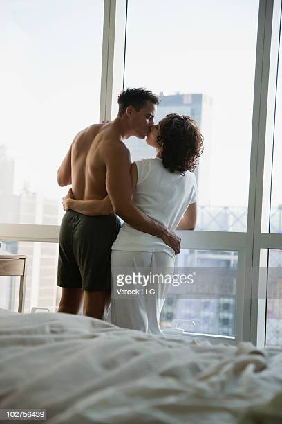 Couple kissing in front of window in hotel room
