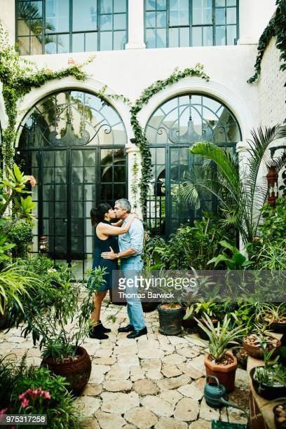 Couple kissing in garden courtyard of home on summer evening