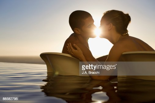 Couple Kissing In Infinity Pool Near Ocean Photo Getty Images