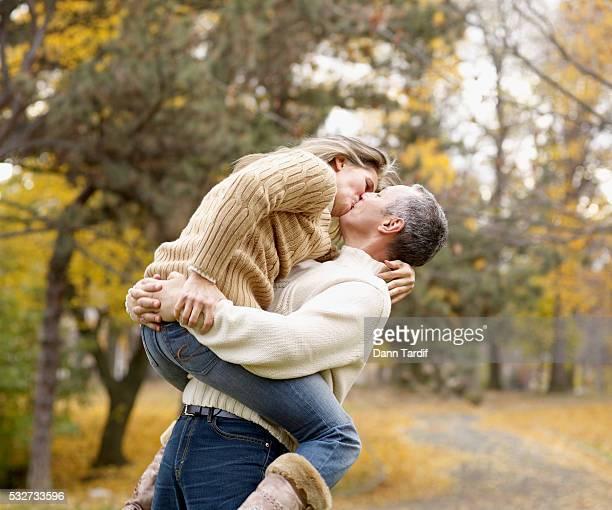 couple kissing in park - 55 59 anni foto e immagini stock