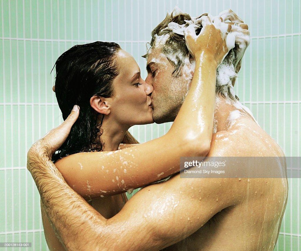 Couple kissing in shower, woman shampooing man's hair : Foto de stock
