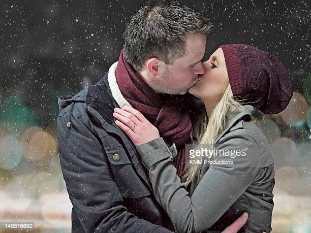 Couple kissing in snow at night