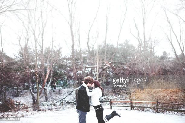 Couple kissing in snowy rural field