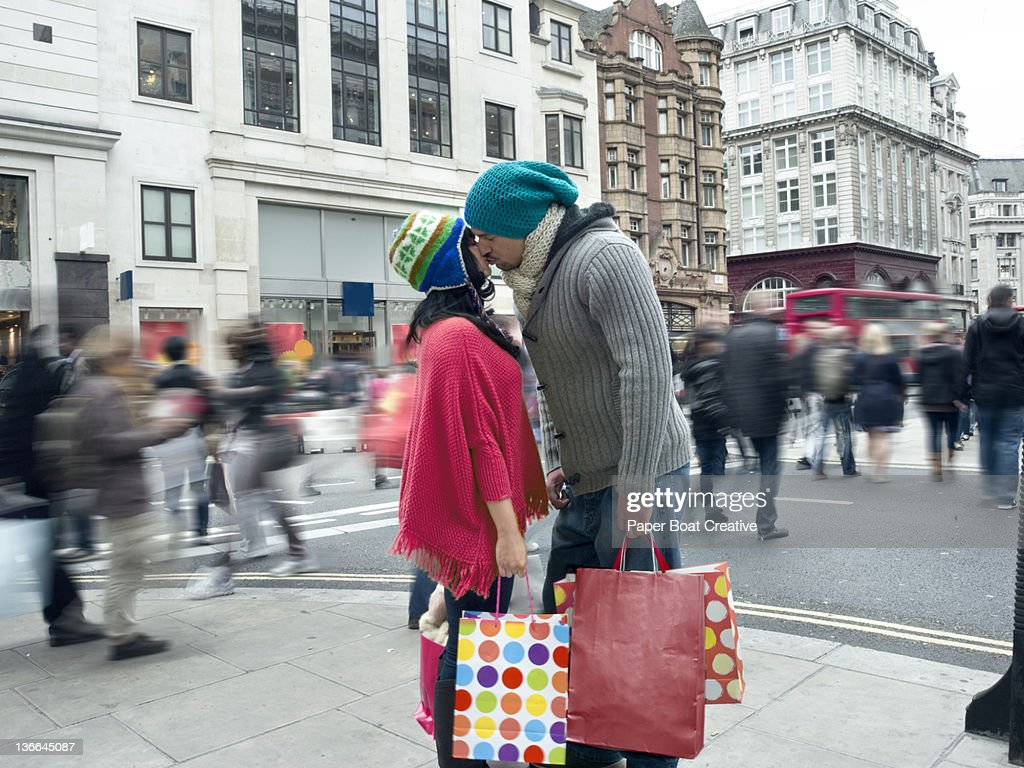 couple kissing in the middle of a busy high street : Stock Photo