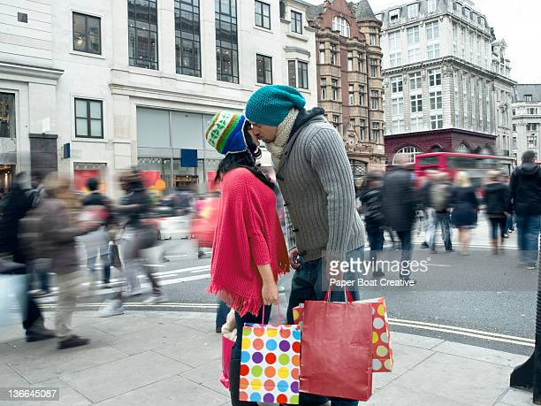 couple kissing in the middle of a busy high street