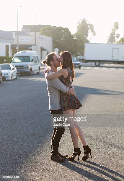couple kissing in the middle of a sunny street