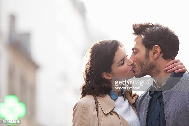 couple kissing in the street - mid adult men foto e immagini stock