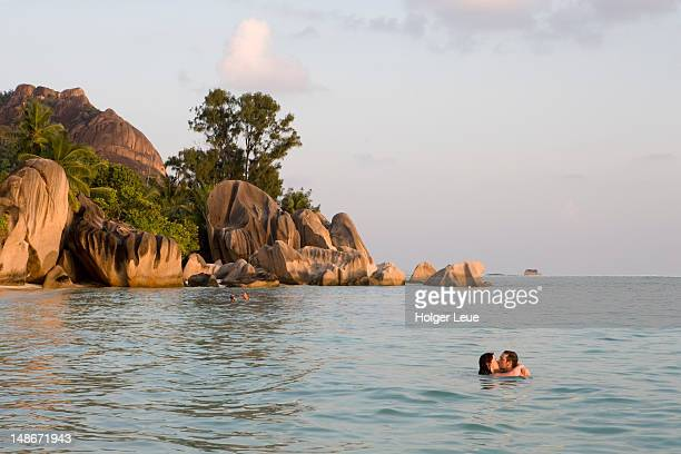 Couple kissing in water at Anse Source d'Argent beach.