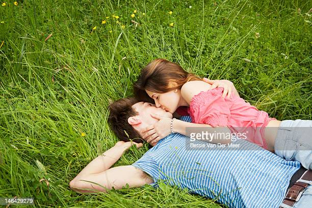 Couple kissing, laying in grass.