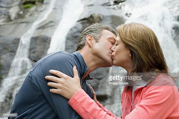 couple embrasser près de la cascade - embrasser sur la bouche photos et images de collection