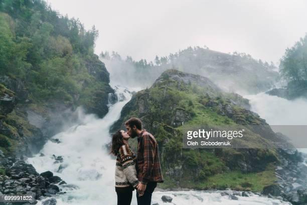 Couple kissing near the Låtefossen Waterfall in mountains in Norway