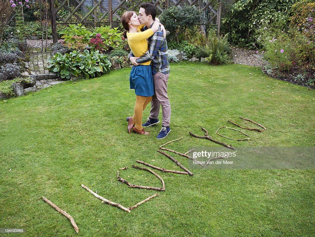 couple kissing next to handmade I love you sign. : Bildbanksbilder