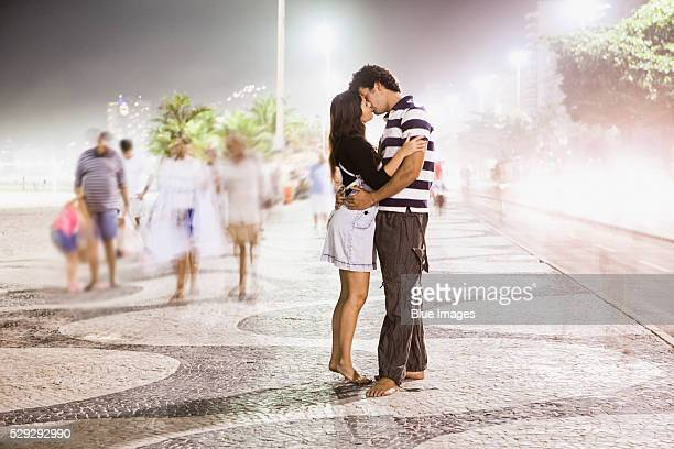 Couple kissing on a busy promenade