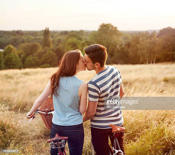 Couple kissing on bikes with view.
