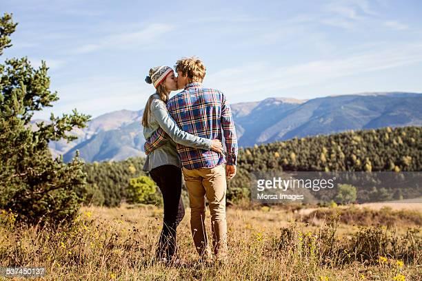 couple kissing on field - besar fotografías e imágenes de stock