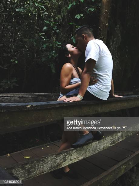 Couple Kissing On Footbridge In Forest