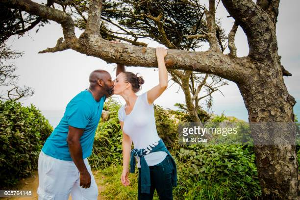 couple kissing on path - black women kissing white men stock pictures, royalty-free photos & images