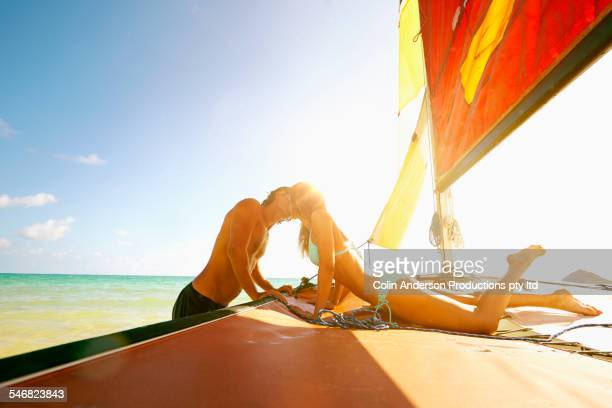 Couple kissing on sailboat in ocean