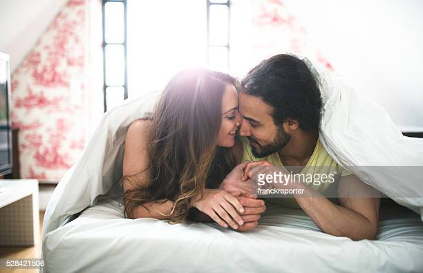couple kissing on the bed on early morning - kissing stock pictures, royalty-free photos & images