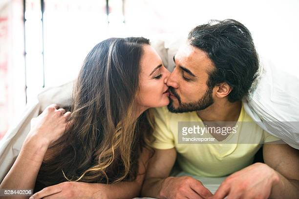 coppia baciarsi sul letto al mattino presto - amanti letto foto e immagini stock