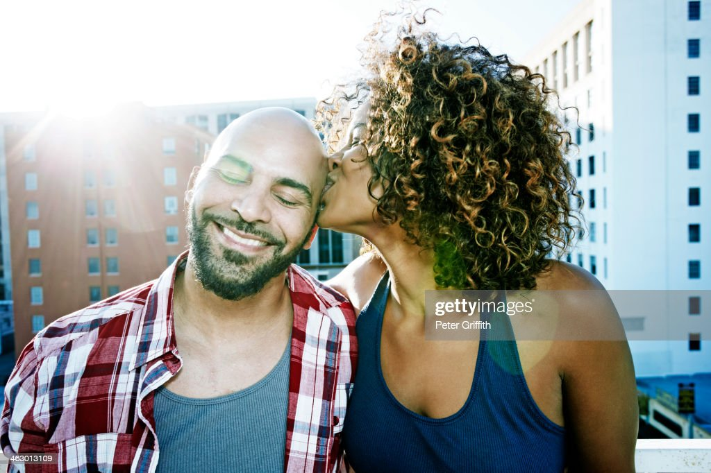 Couple kissing on urban rooftop : Stock Photo