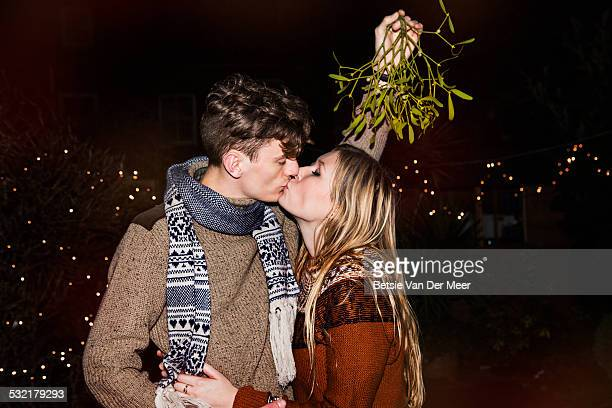 Couple kissing outdoors under mistletoe