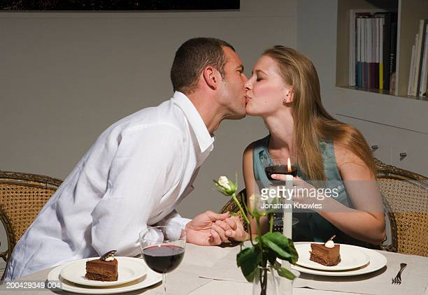 Couple kissing over dessert at candlelit dinner, close-up, side view