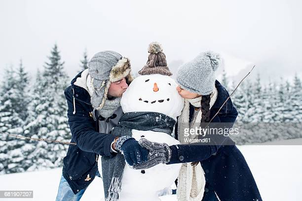 Couple kissing snowman
