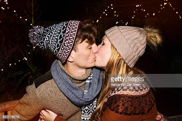 Couple kissing, surrounded by outdoor lights.