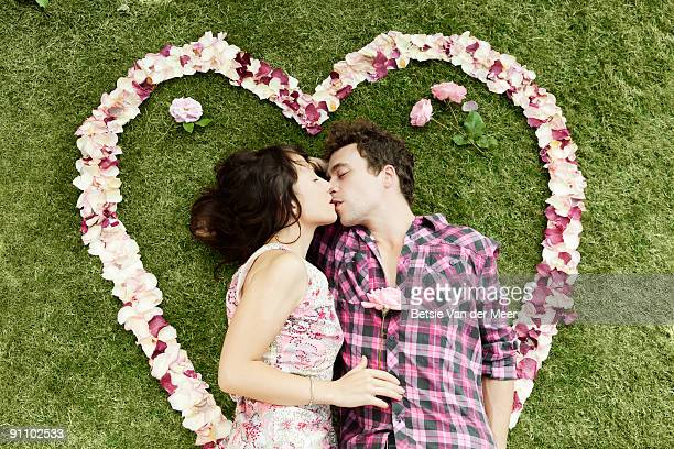 couple kissing, surrounded by rosepedals.