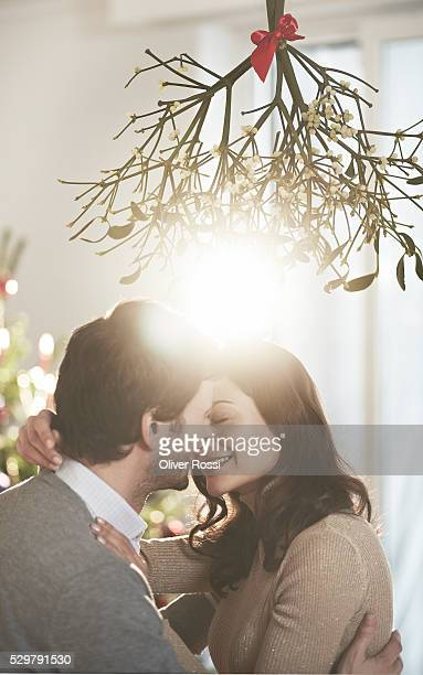 couple kissing under mistletoe at christmas - heterosexuelles paar stock-fotos und bilder