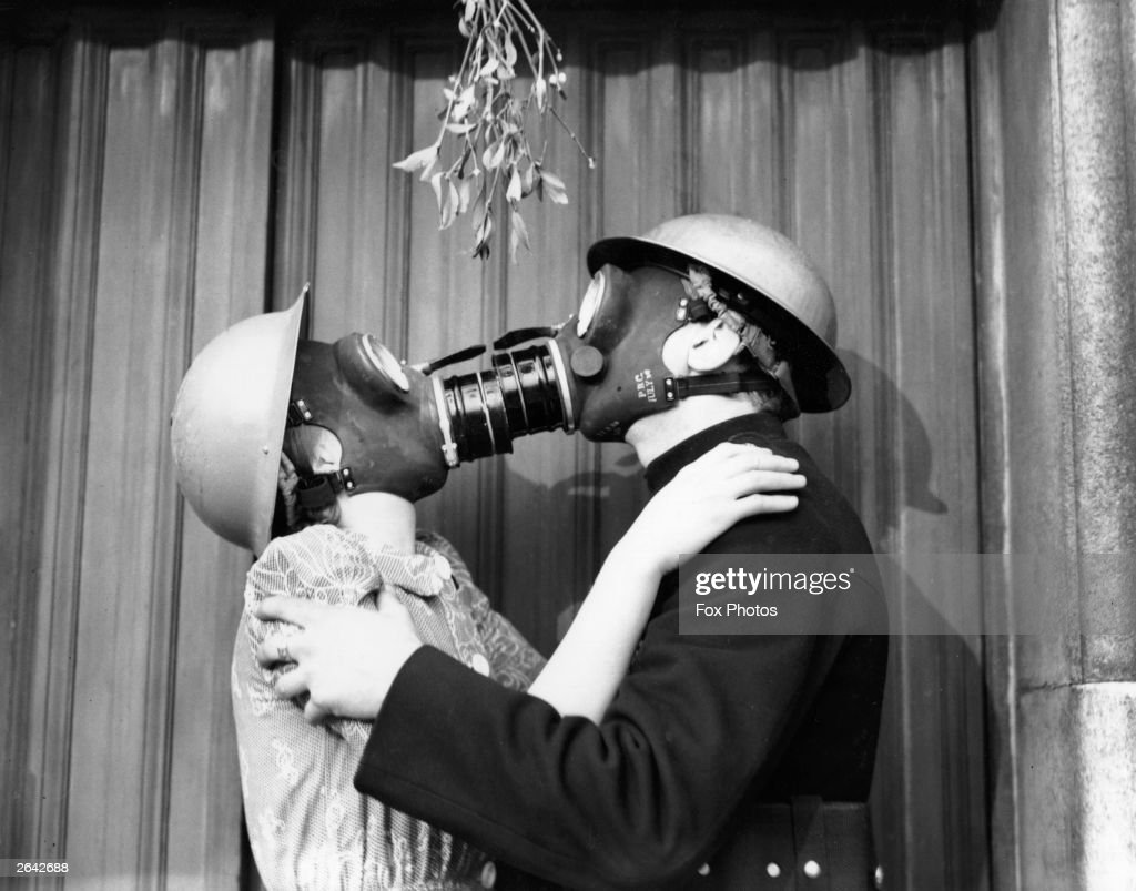 A couple kissing under the mistletoe, wearing gas masks.