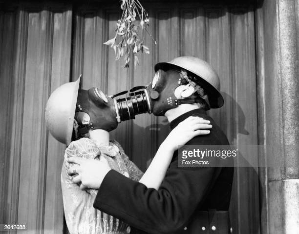 A couple kissing under the mistletoe wearing gas masks