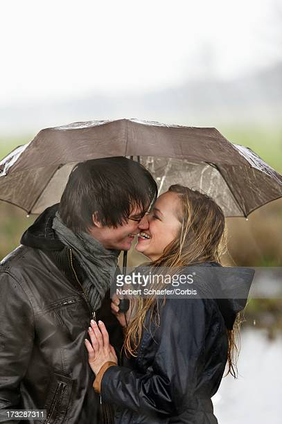 couple kissing under umbrella in rainy day - couples kissing shower stock pictures, royalty-free photos & images