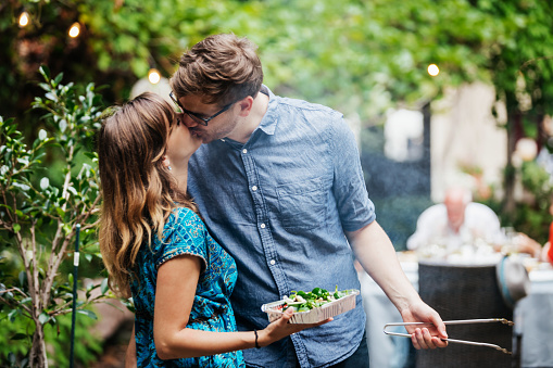 Couple Kissing While Cooking At Family BBQ - gettyimageskorea