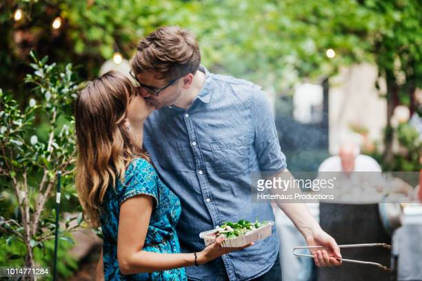 couple kissing while cooking at family bbq - affectionate stock pictures, royalty-free photos & images