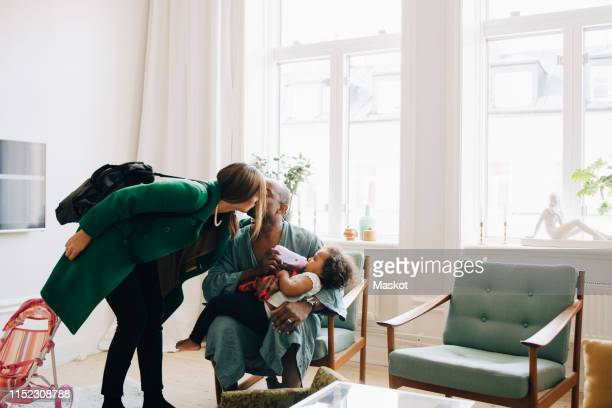 couple kissing while daughter drinking milk in living room at home - stay at home father stock pictures, royalty-free photos & images