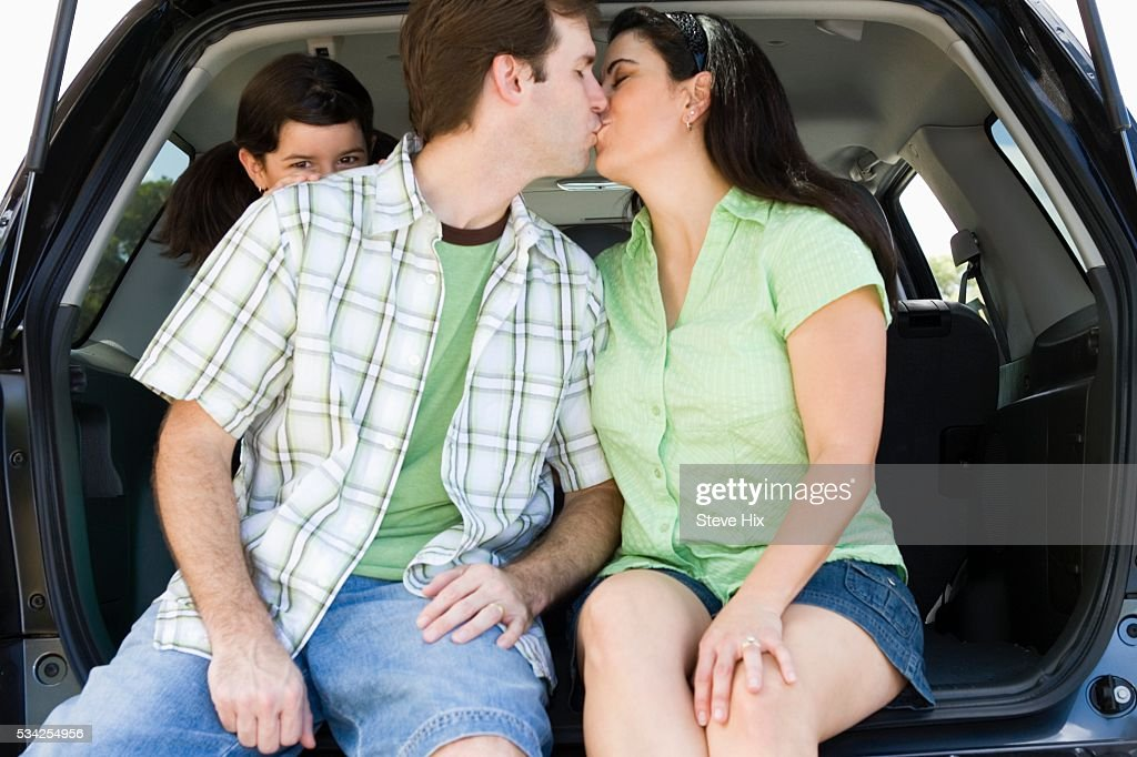 Couple Kissing While Daughter Watches : Stock Photo
