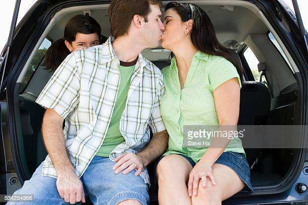 Couple Kissing While Daughter Watches