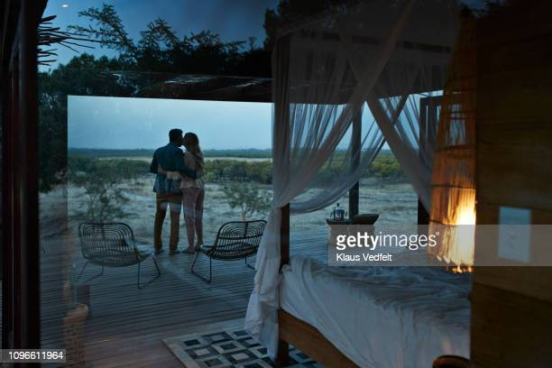 couple kissing while enjoying the view from exclusive cabin - night safari stock pictures, royalty-free photos & images