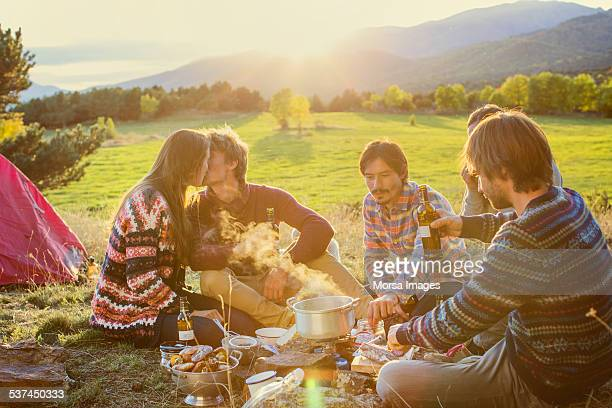 Couple kissing while friends cooking at campsite