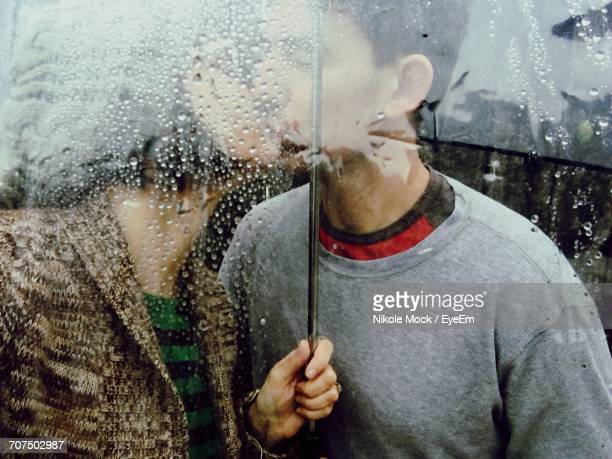 couple kissing while holding umbrella in rainy season - couples kissing shower stock pictures, royalty-free photos & images
