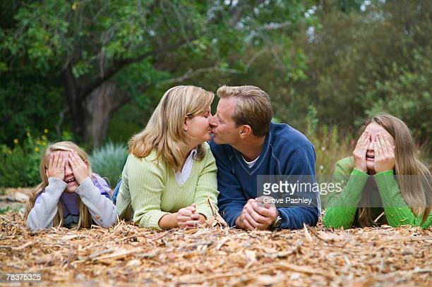 Couple kissing while kids cover eyes