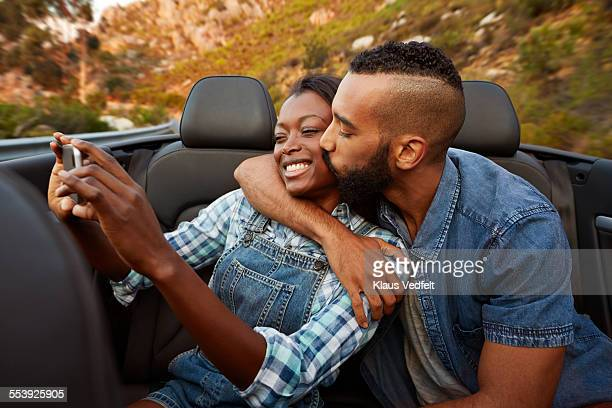 Couple kissing while making selfie in car