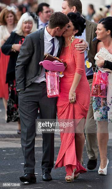 A couple kissing while making their way towards the exit at Aintree after the second day of the annual Grand National meeting known as Ladies' Day...