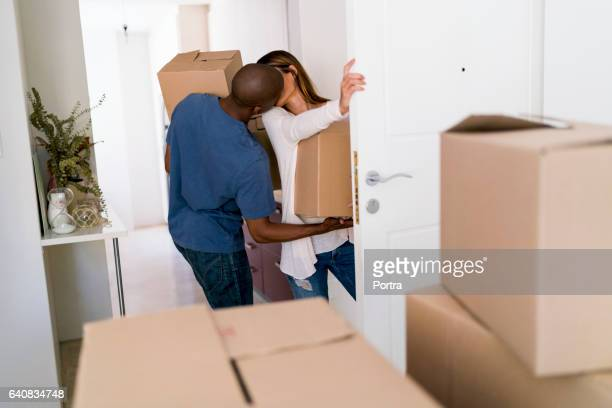 Couple kissing while moving into new house