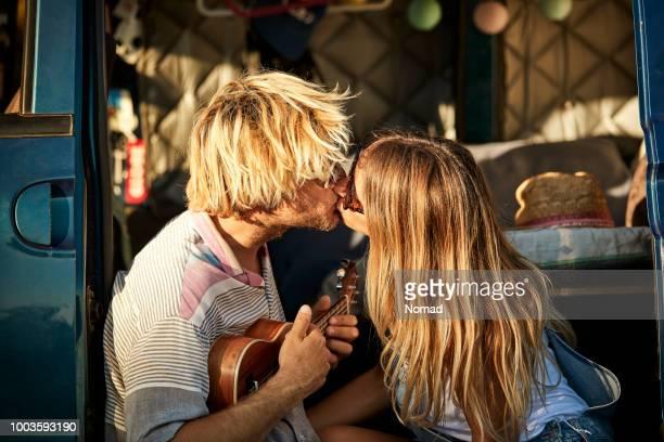 couple s'embrasser tout en se reposant dans la porte du van - embrasser sur la bouche photos et images de collection