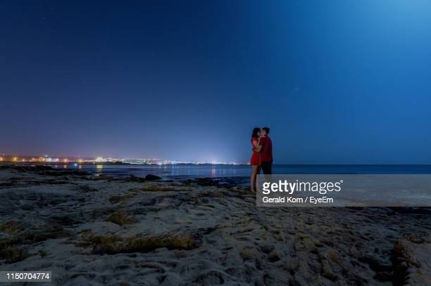 couple kissing while standing at beach against clear blue sky - moonlight lovers stock-fotos und bilder